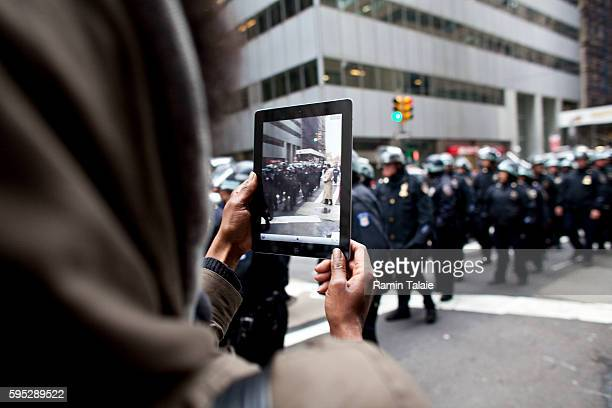 Woman uses an iPad to photograph the police as they follow protestors with Occupy Wall Street movement march on Broadway near Wall Street during day...