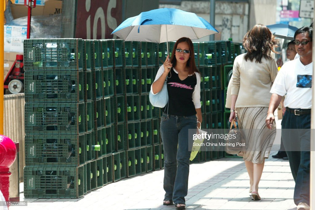 A woman uses an umbrella to avoid the scorching sunshine during Hong Kong's heat wave, which reached 34 degrees this afternoon. Empty water tanks are piled up from nearby offices. 18 July 2005 : ニュース写真