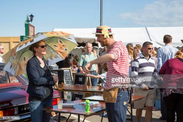 A woman uses an umbrella to shade from the sun at the 2017 Art Car Boot Fair Folkestone Kent