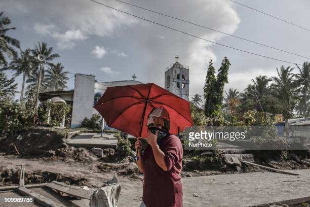 A woman uses an umbrella to shield herself from ashfall as Mount Mayon erupts in Guinobatan Albay province Philippines January 23 2018 Mount Mayon...