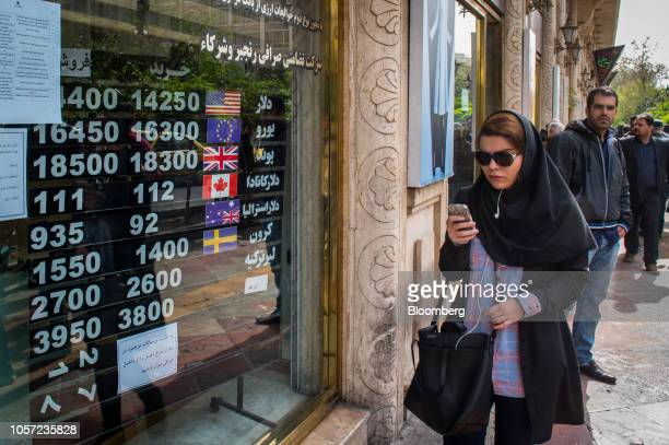 A woman uses as mobile phone as she passes currency exchange rate information in the window of a store in Tehran Iran on Saturday Nov 3 2018 Irans...