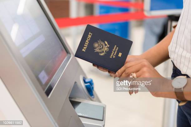 woman uses automated passport control kiosk - passport stock pictures, royalty-free photos & images