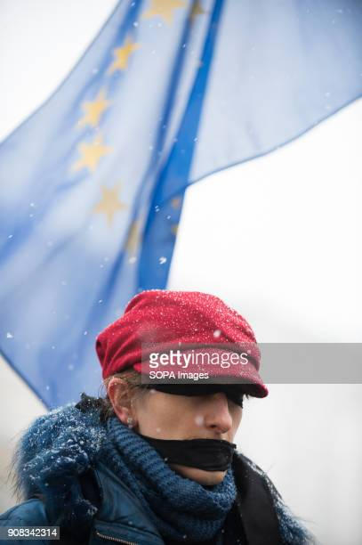A woman uses black bands over her eyes and mouth with the EU flag behind her during a silent assembly named Stolen Justice in Krakow Stolen Justice...