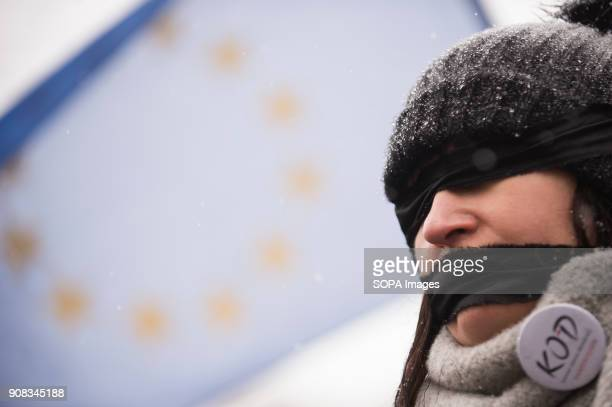 A woman uses black bands over her eyes and mouth with the EU flag behing her during a silent assembly named Stolen Justice in Krakow Stolen Justice...