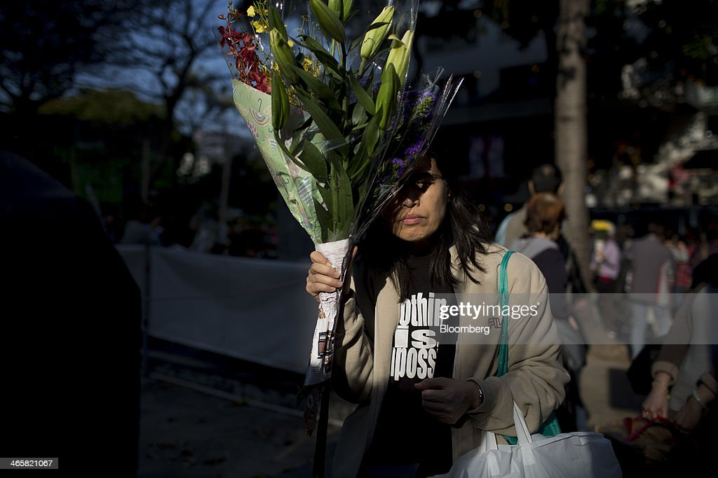 A woman uses bunches of flowers to shield herself from the sun at a flower market in the Mongkok district of Hong Kong, China, on Wednesday, Jan. 29, 2014. The citys financial markets will close early on Jan. 30 for the Chinese New Year holidays and resume trading on Feb. 4, while those in the mainland will be shut from tomorrow through Feb. 6. Photographer: Brent Lewin/Bloomberg via Getty Images