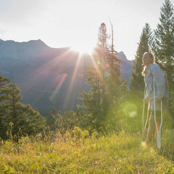 Woman uses crutches to stand in meadow, below mountains