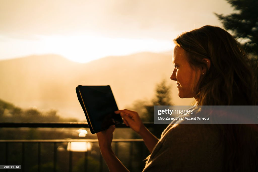Woman uses digital tablet against backdrop of sunrise : Stock-Foto