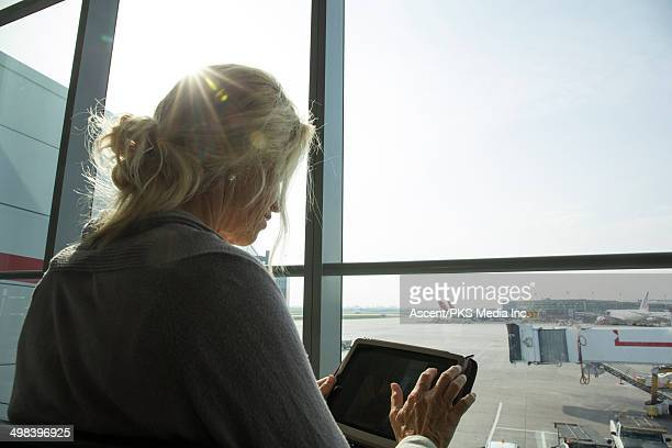 Woman uses digital tablet at airport, sunrise