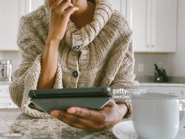 woman uses digital tablet at kitchen counter - parte del cuerpo humano fotografías e imágenes de stock