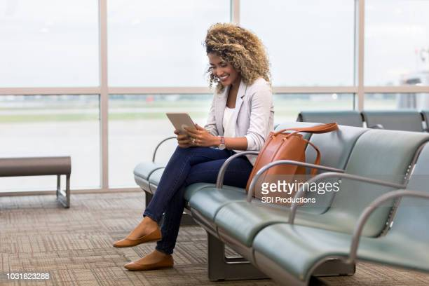 Woman uses digital tablet in airport terminal