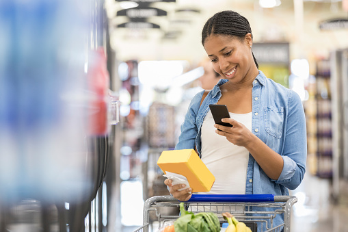 Woman uses grocery store mobile app while shopping - gettyimageskorea