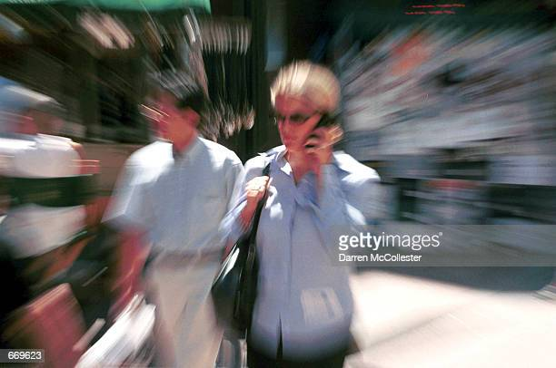 A woman uses her cell phone in Boston MA while walking down the street July 19 2000 Recently the Cellular Telecommunications Industry Association...