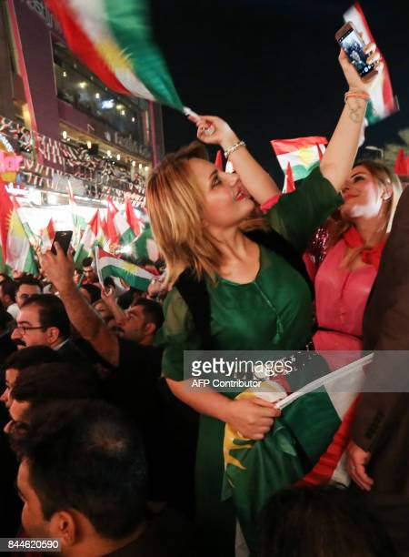A woman uses her cellphone to take a selfie photograph during a celebration of Iraqi Kurds urging people to vote in the upcoming independence...