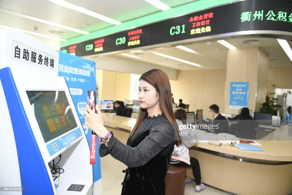 A woman uses her 'electronic ID card' in the mobile payment app Alipay to verify herself as she checks her house accumulation fund and social security fund on April 17, 2018 in Hangzhou, Zhejiang Province of China. 'Electronic ID card' will allow users to check in and go through security checks at railway stations and airports without showing their original ID cards and will be tested in Quzhou, Hangzhou and Fuzhou this April.