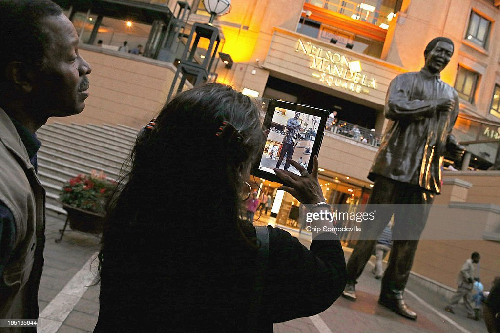 A woman uses her iPad to make a photograph of the 20-foot-tall statue of former South African President Nelson Mandela in the shopping square named after the anti-apartheid hero April 1, 2013 in Johannesburg, South Africa. Mandela, 94, is recovering from pneumonia in hospital, his third stay in the last four months. Mandela's lungs were damaged when he contracted tuberculosis during his 27 years in the infamous Robben Island prison. Mandela became the nation's first democratically elected president in 1994 following the end of apartheid.
