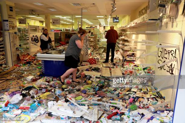 TOPSHOT A woman uses her mobile phone as she stands in a looted Budnikowsky drugstore in Hamburg's Schanzenviertel district on July 8 2017 in Hamburg...