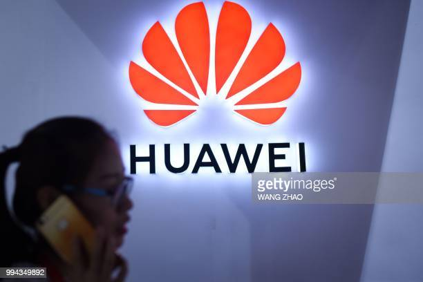 A woman uses her mobile phone in front of a LED display board of Huawei at Beijing International Consumer Electronics Expo in Beijing on July 9 2018
