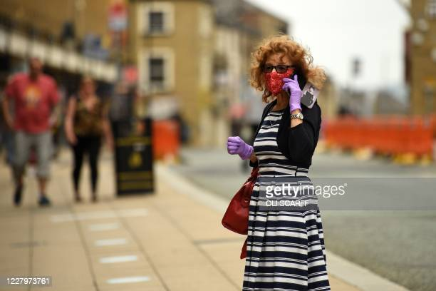 A woman uses her mobile phone in the street wearing PPE in the form of gloves and a protective face covering as precautions against the transmission...