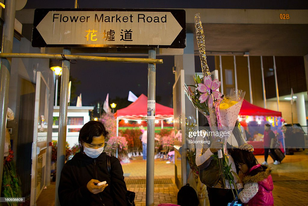 A woman uses her mobile phone on Flower Market Road in the Mongkok district of Hong Kong, China, on Thursday, Feb. 7, 2013. Hong Kong's stock market will be shut for three days next week for the Lunar New Year holidays, while markets in mainland China will be closed for the whole week. Photographer: Lam Yik Fei/Bloomberg via Getty Images