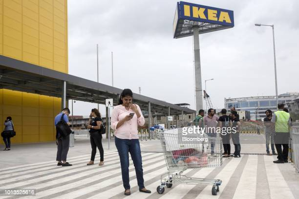 A woman uses her mobile phone outside the Ikea retail store in Hitech City on the outskirts of Hyderabad India on Wednesday Aug 8 2018 In a milestone...