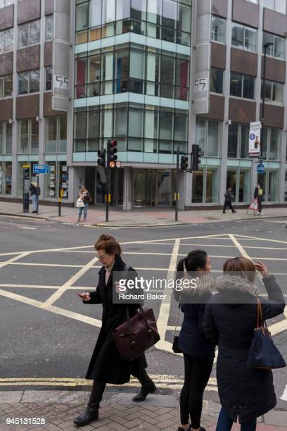 A woman uses her mobile phone outside the offices of Cambridge Analytica on New Oxford Street the UK tech company accused of harvesting the personal...