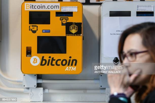A woman uses her phone as she walks past an ATM machine for digital currency Bitcoin in Hong Kong on December 18 2017 Bitcoin has soared in recent...