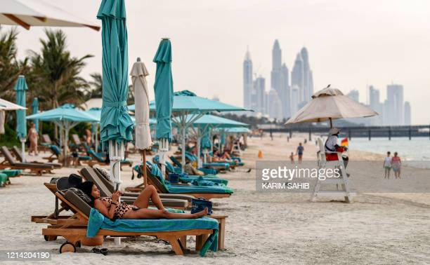 Woman uses her phone while on a lounge chair at the Jumeirah al-Naseem beach in Dubai on May 20 as COVID-19 coronavirus pandemic lockdown measures...