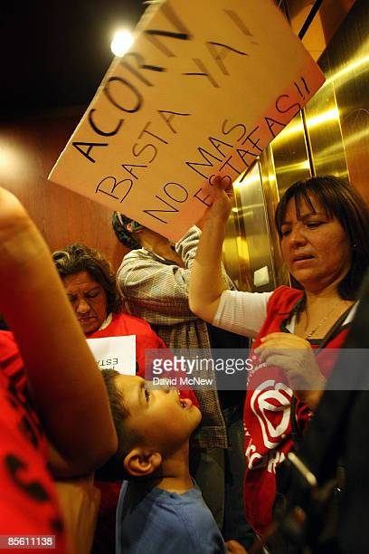 A woman uses her placard to fan an autistic boy when homeowners and ACORN activists become stuck in an elevator as they visit the new offices of the...