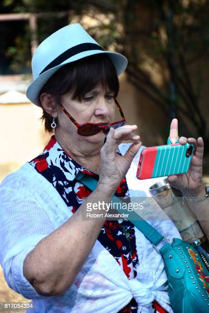 A woman uses her smartphone to take a photograph at a Fourth of July celebration in Santa Fe New Mexico