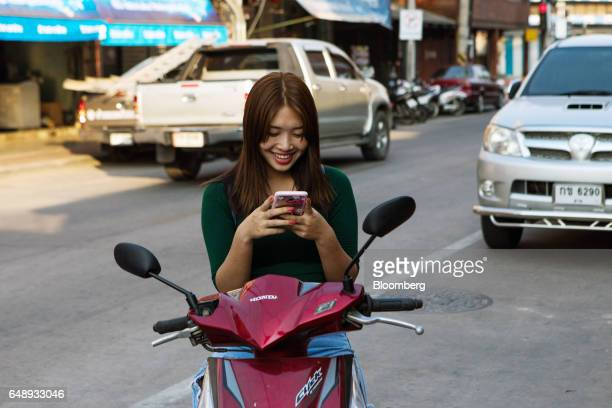 A woman uses her smartphone while seated on a motorcycle in Nan Nan Province Thailand on Friday March 3 2017 After more than a year of disinflation...