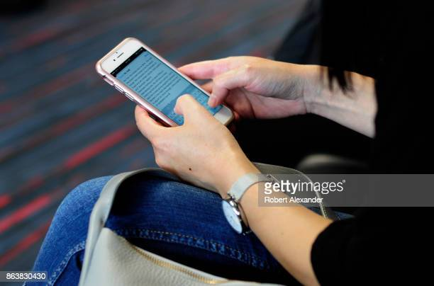 A woman uses her smartphone while waiting to board a plane at the Dallas/Fort Worth International Airport located roughly halfway between Dallas and...