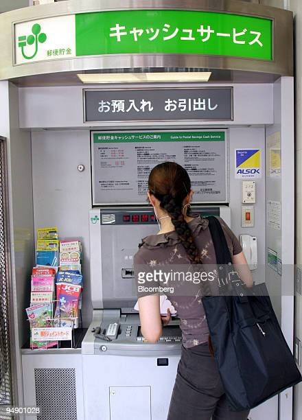 A woman uses Japan Post ATM at a post office in Tokyo Friday August 5 2005 Japanese Prime Minister Junichiro Koizumi will ask upper house lawmakers...