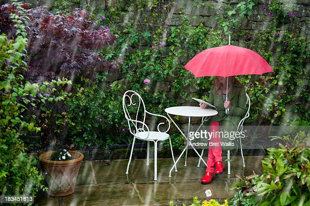 Woman uses laptop in the garden despite the rain