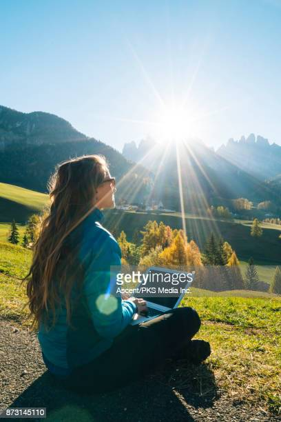 Woman uses laptop overlooking valley, mountains and sunrise