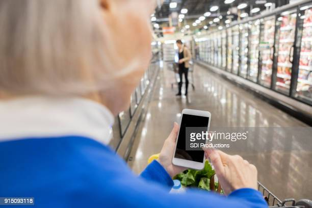 woman uses mobile app in supermarket - touchpad stock pictures, royalty-free photos & images