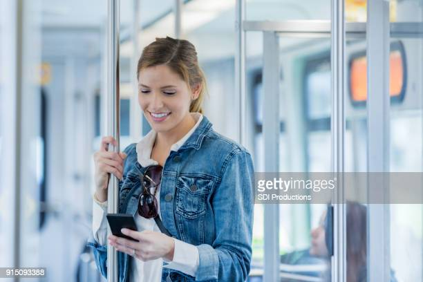 Woman uses mobile app while riding commuter train