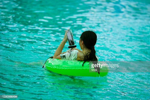 A woman uses mobile phone at Dongqian Lake water park on June 18 2020 in Ningbo Zhejiang Province of China
