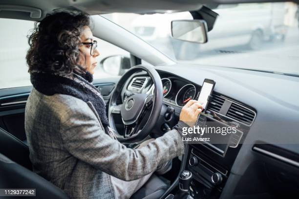 woman uses navigation on her mobile phone in the car - image stock pictures, royalty-free photos & images