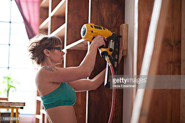 Woman uses power tools for carpentry