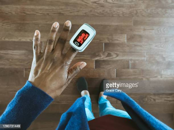 woman uses pulse oximeter - pulse oximeter stock pictures, royalty-free photos & images