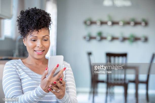 woman uses smart phone for virtual doctor's appointment from home - facetime stock pictures, royalty-free photos & images