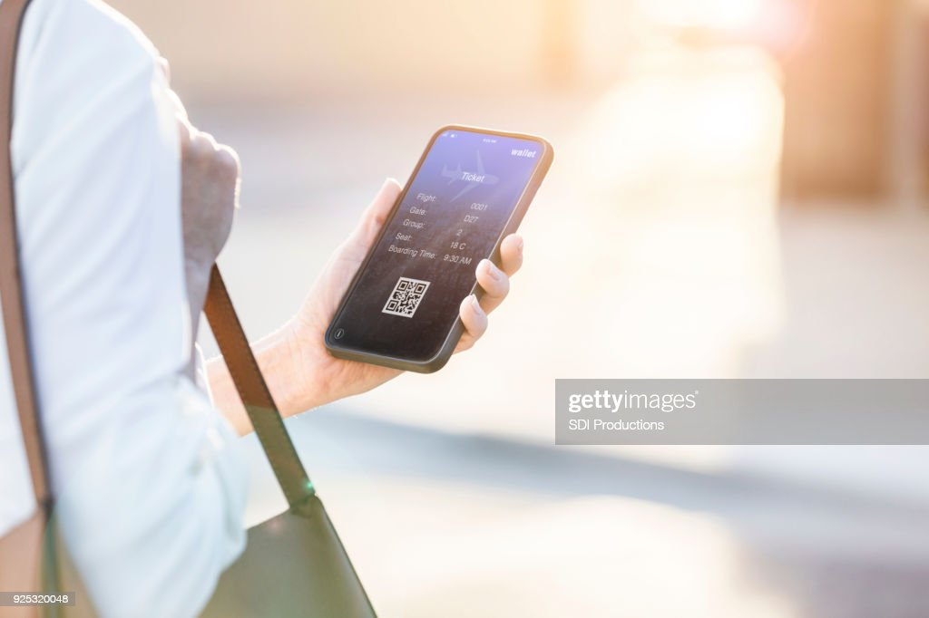 Woman uses smart phone to book travel reservation : Stock Photo