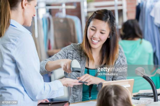 Woman uses smart phone to pay for purchase