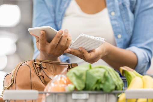 Woman uses smart phone while shopping - gettyimageskorea