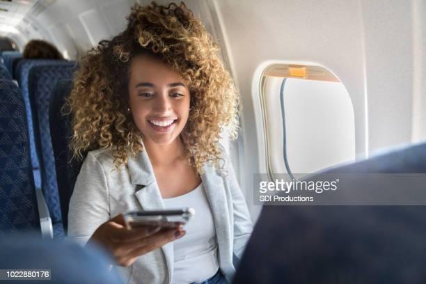 女性が飛行機の中でスマート フォンを使用してください。 - 乗り物に乗って ストックフォトと画像