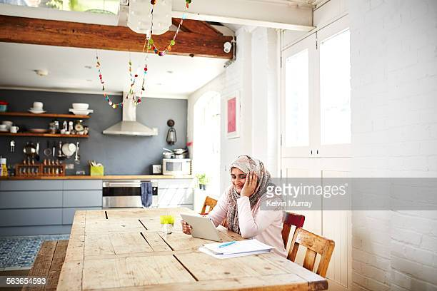 woman uses tablet while sitting at a table - cardigan sweater stock pictures, royalty-free photos & images