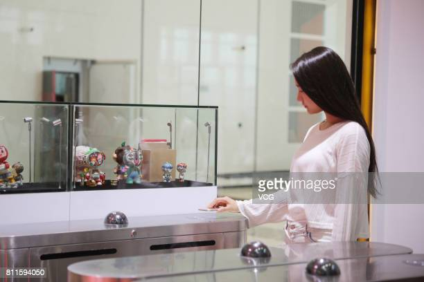 A woman uses the Ant Financial Services Group's Alipay app to scan the QR code as she enters the Alibaba Selfservice Store 'Tao Cafe' during the...