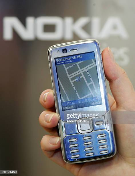 Woman uses the navigate tool on the Nokia N82 cell phone with an internal GPS receiver and Nokia map, at the CeBIT technology fair the first day the...