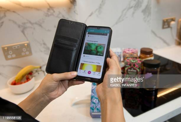 Woman uses the Olio mobile app to look for food goods to swap with other uses, in this posed photograph taken in north London on January 22, 2020. -...