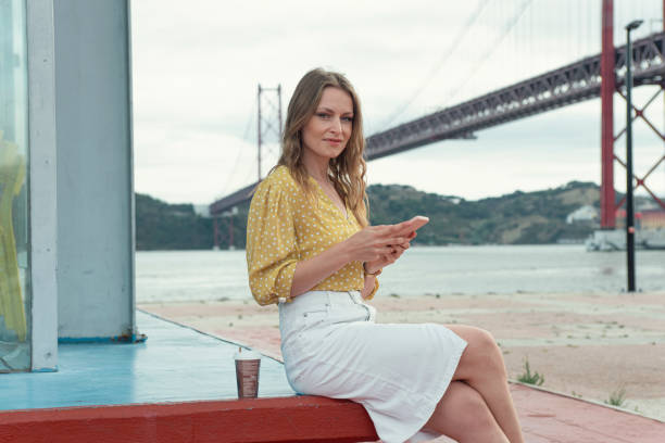 Woman uses the phone sitting along the River Tagus in Lisbon
